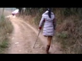 Chinese LAK amputee girl crutching on village path
