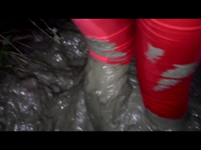 A girl in rubber boots with high heels and red jeans in deep mud MOV 0125 2607