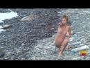 Нудистка заряжается на берегу моря