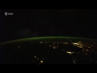 Stars and city lights revolve and seem to form from a point behind the green atmosphere of our planet. #timelapse