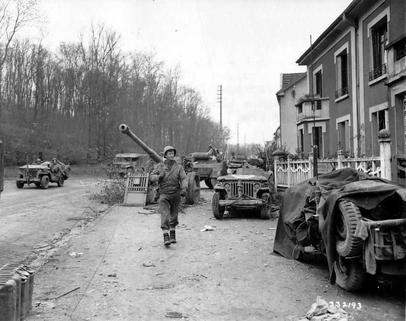 Рядовой 95-й американской пехотной дивизии Джексон идет по улице пригорода французского городка Мец мимо джипов и немецкой 88-мм пушки PaK 43.