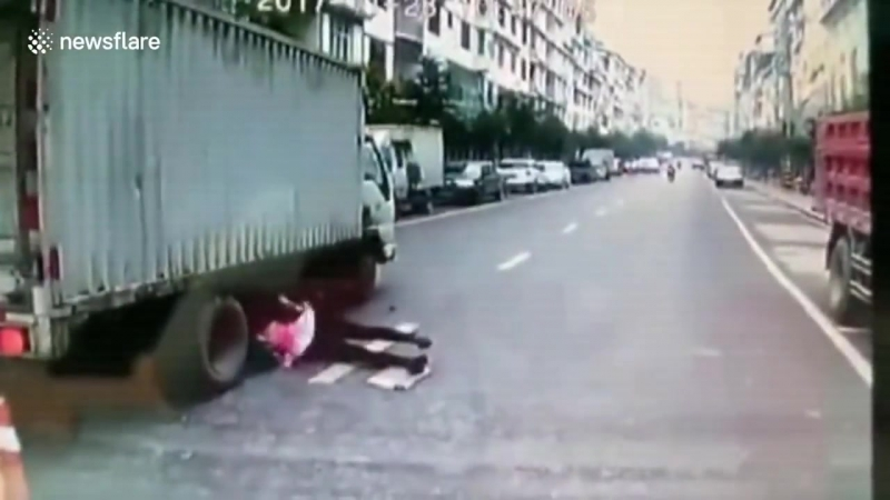 Woman crossing road narrowly escapes being run over by lorry