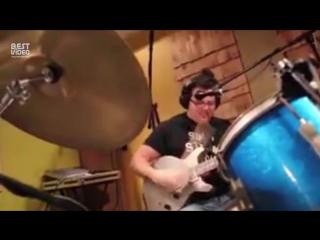 Парень одновременно играет на гитаре, барабанах и поет