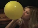 Lexi blows up a yellow balloon until it pops