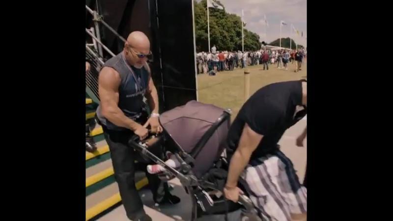 Билл Голдберг помогает спускать коляску с ребёнком.