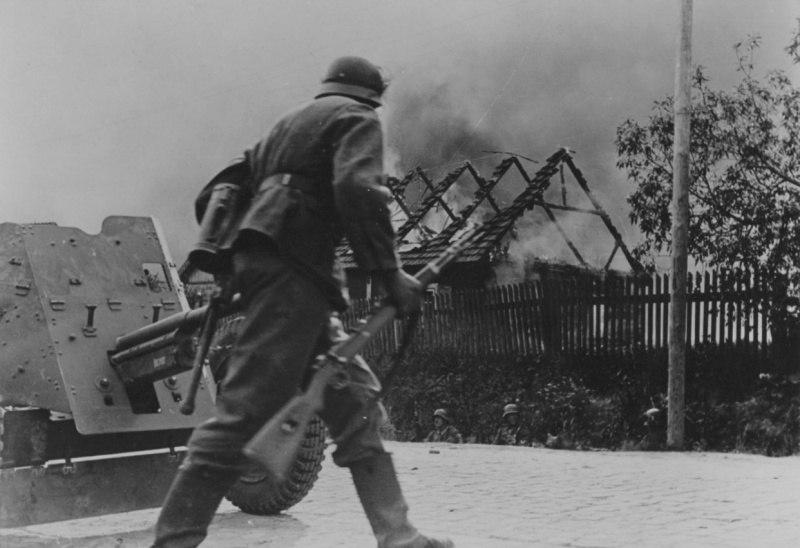 Немецкий солдат переходит улицу горящей советской деревни у 37-мм противотанковой пушки PaK 35/36. Фотография опубликована на обложке американского журнала Newsweek от 20 октября 1941 года.