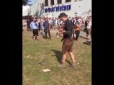 Толпа наблюдает как мужик пьяный пытается надеть кросовку и поддерживает его