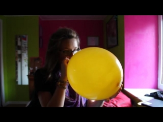 Scared girl blowing up a balloon to shreds.mp4