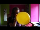 Scared girl blowing up a balloon to