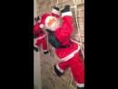 Уличные фигуры Дедов Морозов на веревочной лестнице