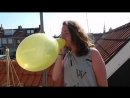 Girl blows up a yellow balloon until it pops on a