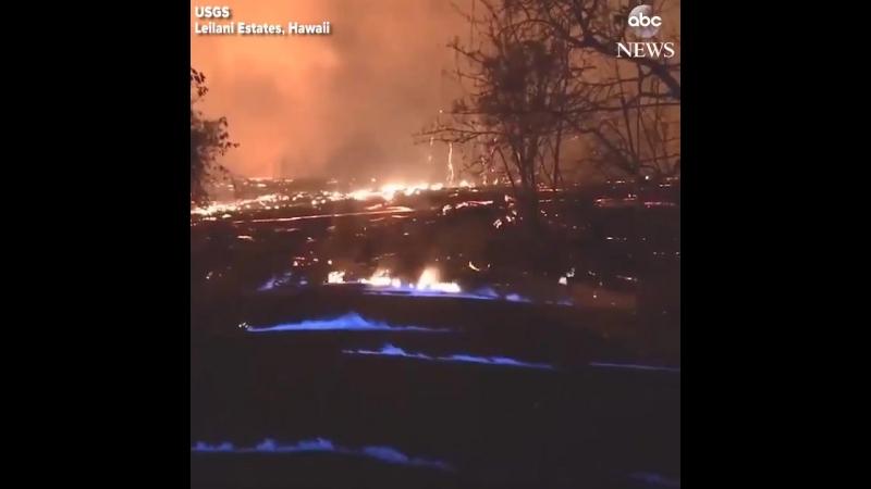 Синее пламя от сжигания метана возникающего из трещин в дороге во время продолжающегося извержения вулкана Килауэа. -ABC