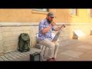 Уличный музыкант в Питере играет на пиле.