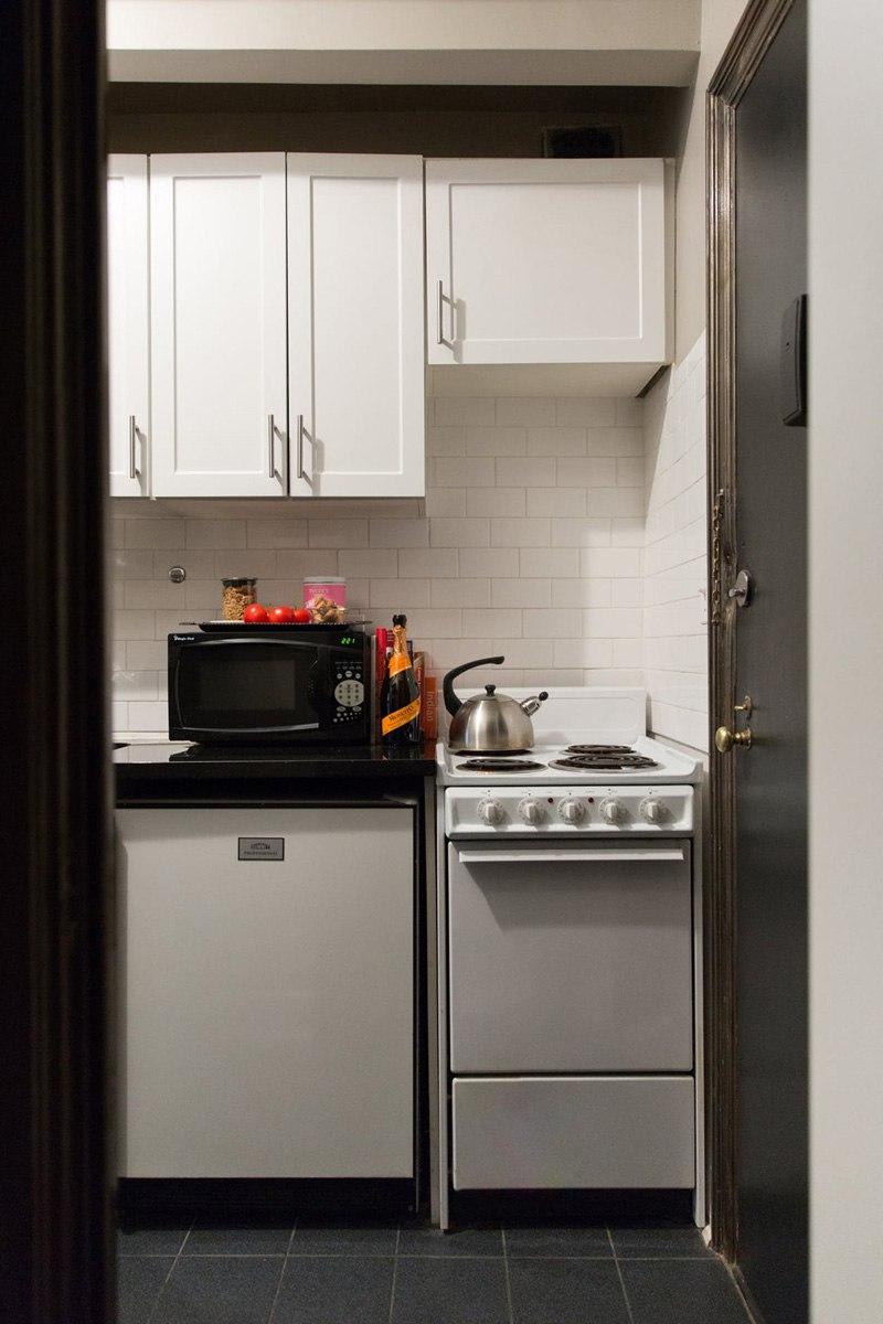 Жилая студия дизайнера: 32 м с черными стенами и кухней в прихожей.