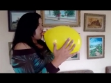 Woman blows to pop a yellow balloon in her living room.mp4
