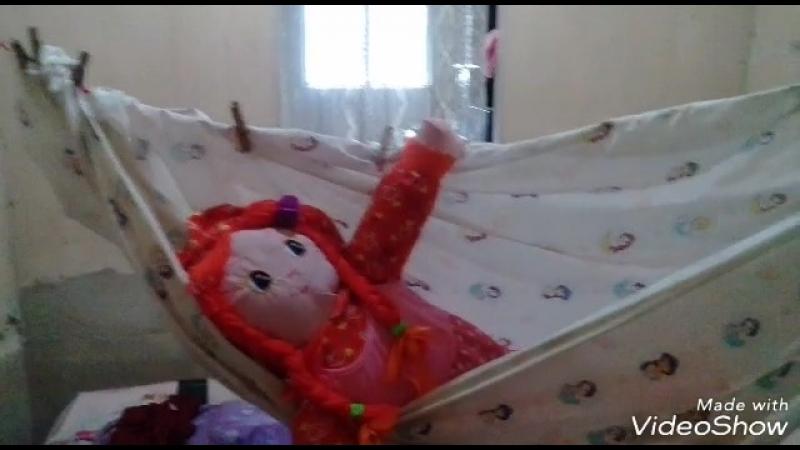 Boneca se balançando na rede