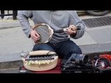 Уличный музыкант играет на теннисной ракетке