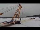Трактор пытается вытянуть утонувшие Уралы