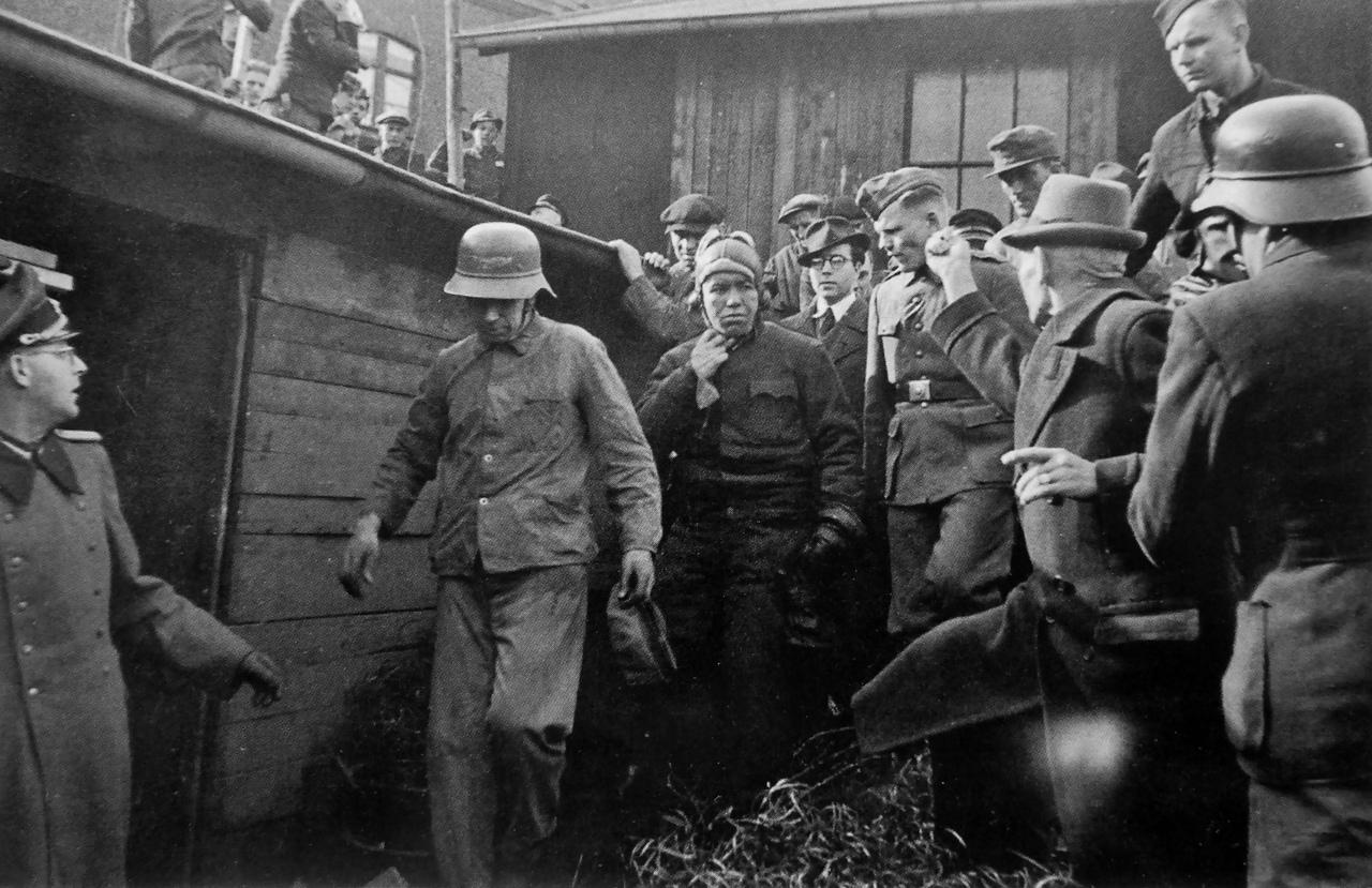Житель Эссена грозит кулаком пленному американскому летчику. Третий Рейх. Июнь-август 1944 года.