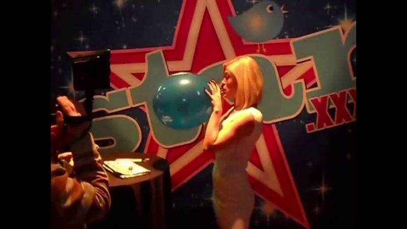 Balloon challenge at an expo girl blows to pop