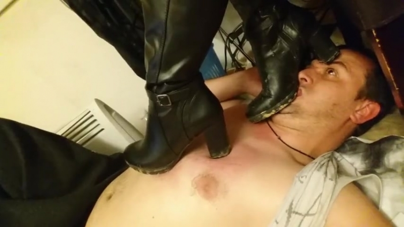 Footstool lick dirty black boots in home