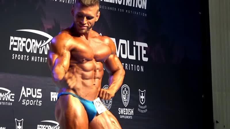 Bodybuilder Piotr Borecki onstage posing at FIWE Warsaw 2017