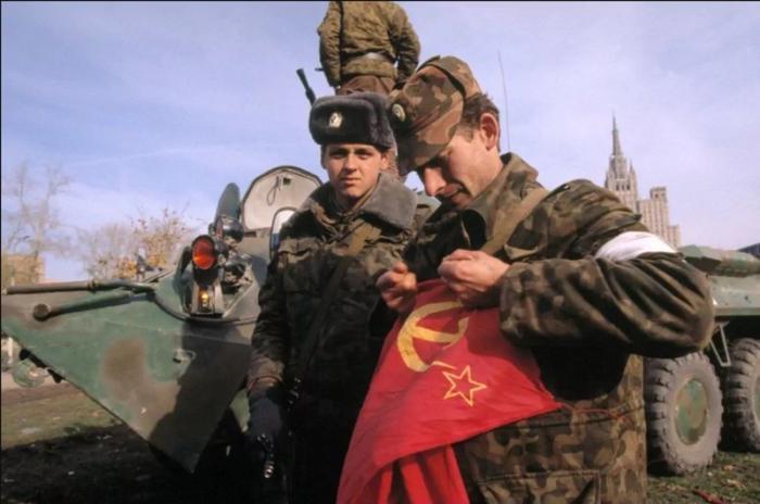 Офицер Таманской дивизии рвет Красный флаг, снятый со здания Дома Советов, октябрь 1993 года.