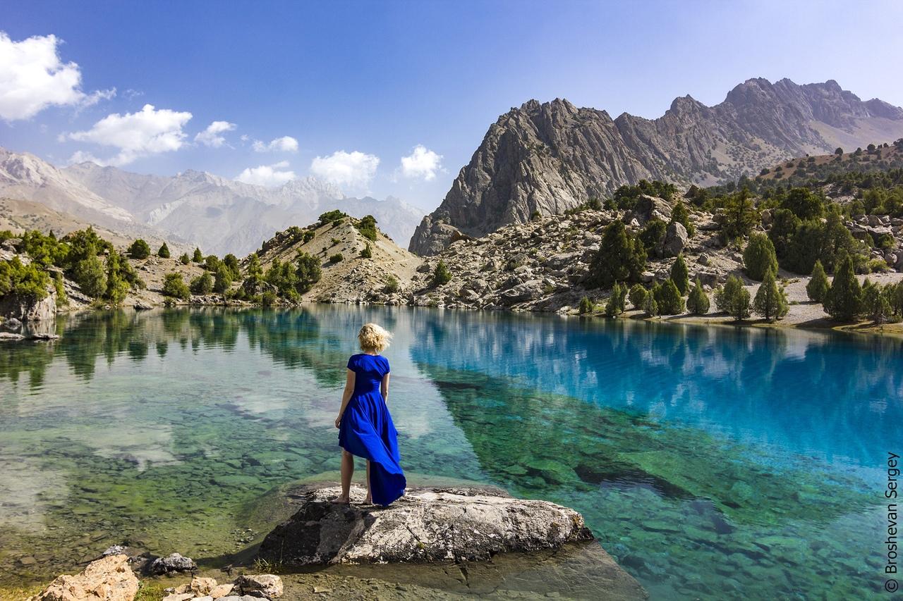 девушка в синем платье на фоне ярко-голубого озера в Фанских горах со скалами на фоне