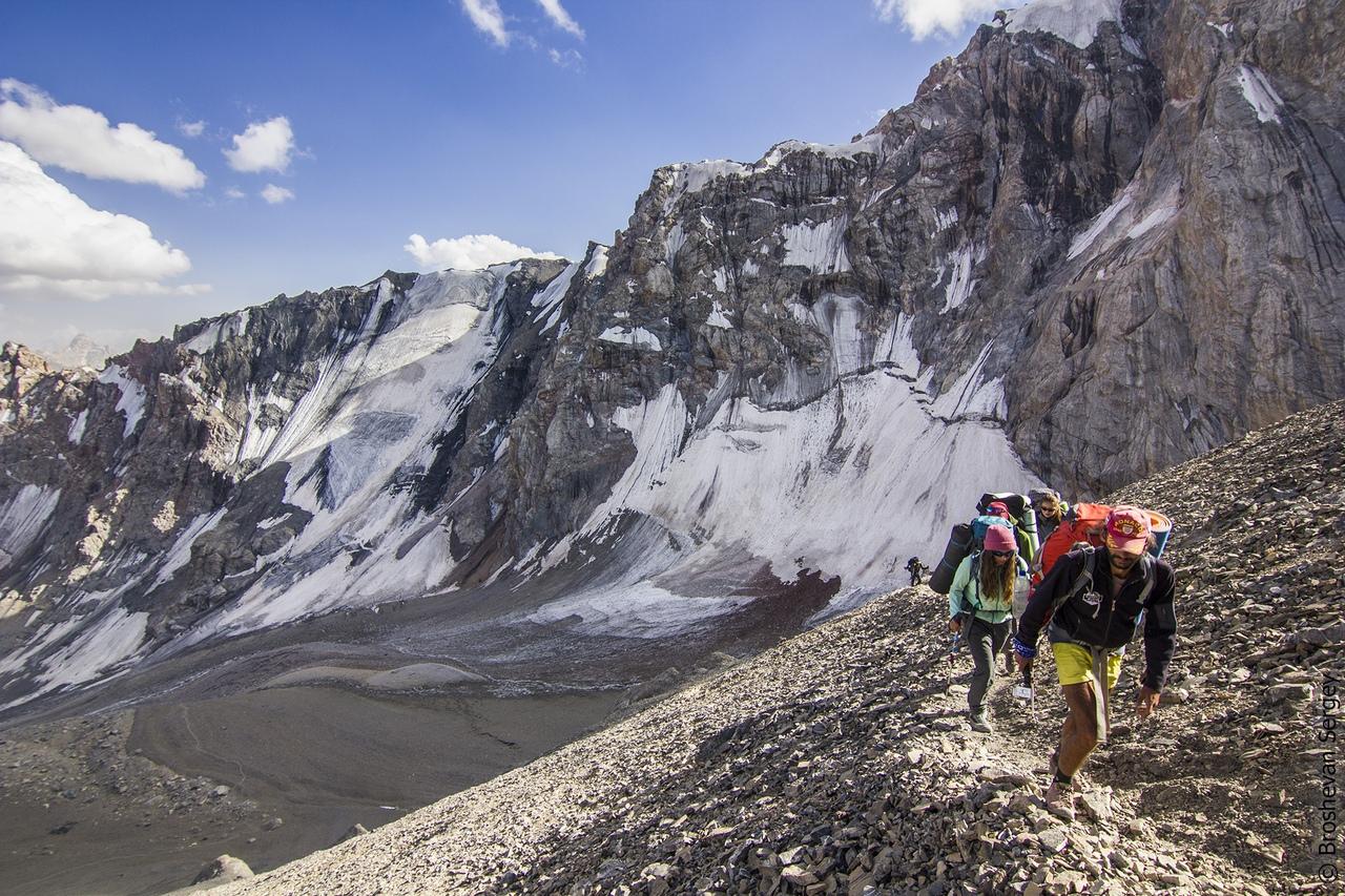 группа туристок идет с рюкзаками по осыпному склону на фоне ледников