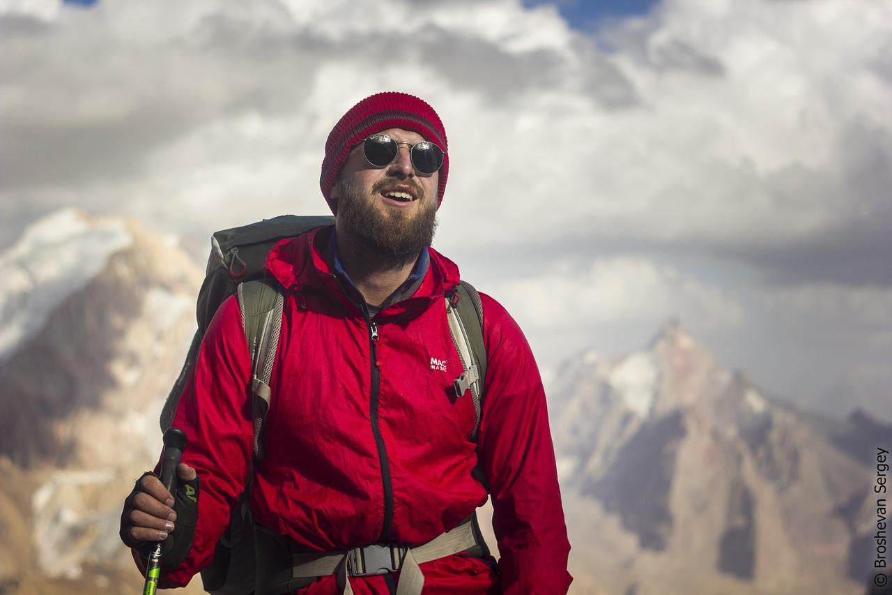 парень с рюкзаком в очках на фоне гор