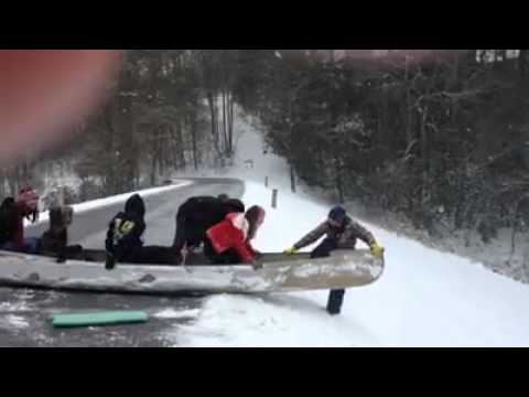 Canoe Slides Down Snowy Hill into Lake