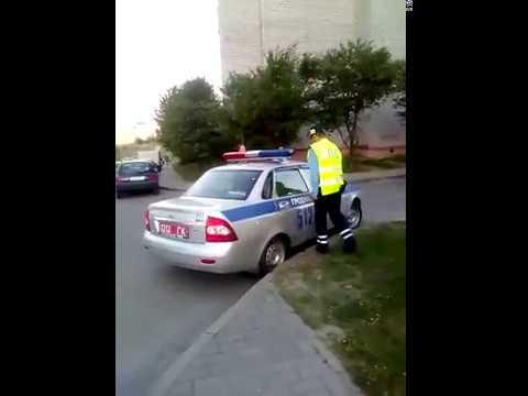 сотрудники ГАИ заталкивают женщину в служебную машину