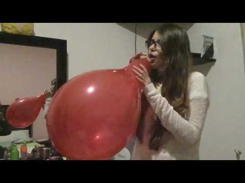 Cute nerdy girl blowing to pop a huge red balloon
