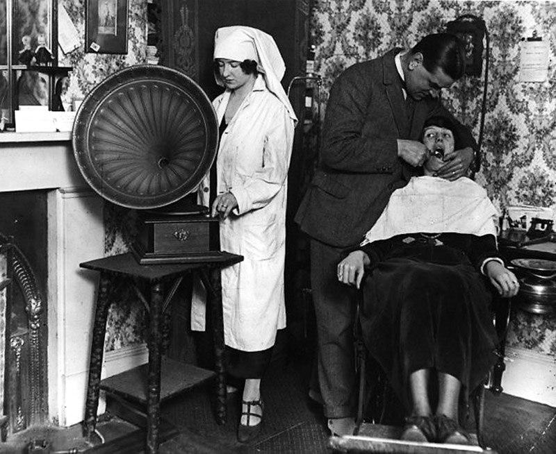 Помощница стоматолога заводит граммофон, чтобы отвлечь пациента от боли, 1922 год