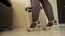 ladies legs in nylon pantyhose with a pattern and sandals on high heels