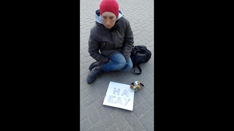 Молодая БОМЖиха сидит на тротуаре с детской игрушкой и табличкой На еду