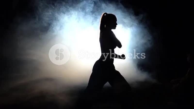Girl-athlete-shows-power-moves-black-silhouette-backlight_sctuvzmi__PM