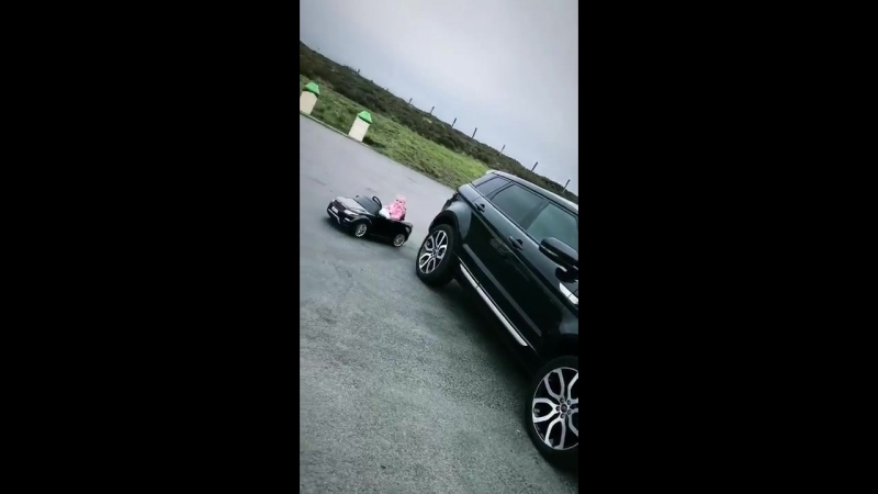 Baby rides mini Range Rover from behind an actual Range Rover