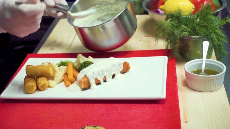 Шеф-повар ресторана Zaferan готовит лосось с овощами.