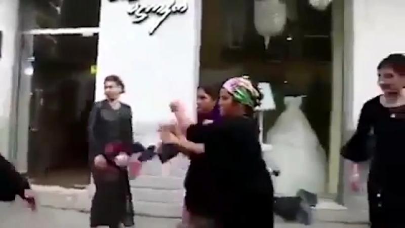 Женщина посреди оживленной улицы бьет мужчину маленьким ребенком
