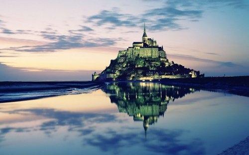 Скалистый остров Мон-Сен-Мишель, отражающийся в воде (Франция).