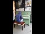 Уличный музыкант играет современные мелодии на пианино