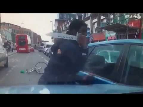 Cyclist carrying a huge zombie knife attacks a young motorist in his car