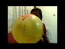 Girl blowing up a huge yellow balloon until it bursts