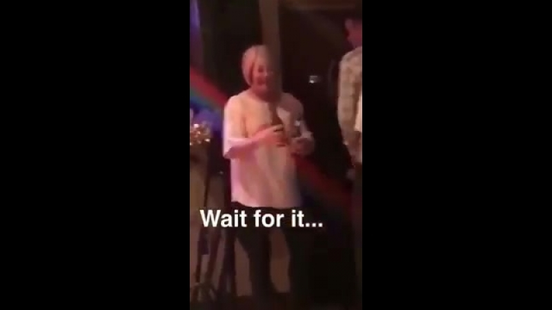 Old woman using beer bottles as musical instruments, smashes them