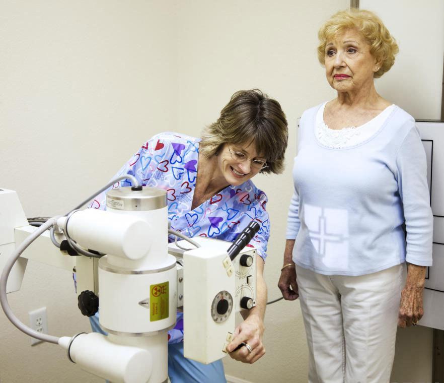 Рентгеновский техник готовится взять рентген пациента.