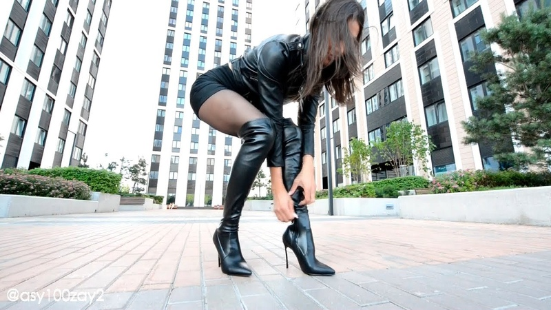 Walking in overknee boots and leather mini skirt platform high heels long legs
