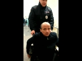 Полицейский помогает инвалиду в метро.