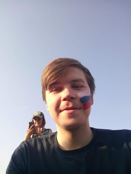 Смотрим футбол на фестивале болельщиков.  Мне вот та девочка за 200 рублей нарисовала флаг на лице. Настя посмотрела, но не подала виду, что там розовый и это очень видно. Ну и такие большие я больше рисовать не буду — любое прикосновение (а чешется же от пота на палящем солнце) и всё содрано.  23 июня 2018