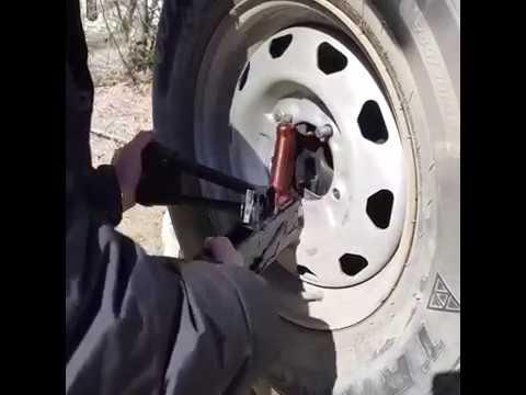 Мужики с помощью автомата Калашникова открутили запасное колесо на автомобиле .